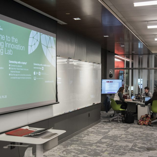 Inside of the Teaching Innovation Learning Lab Classroom with large screens, mobile desks, and students interacting.